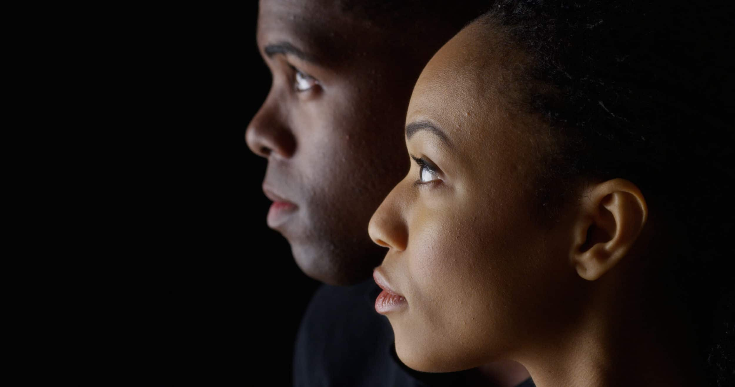Dramatic profile of Black man and woman looking up